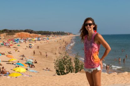 Tegan standing at the beach in Vilamoura, lots of people behind her