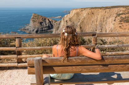 Tegan sitting on the seat overlooking the sea, sun lighting her up