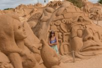 Tegan standing amongst the sand sculptures