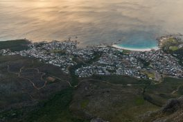 looking down at the tiny houses from the top of table mountain, different shades of blue at the beach below