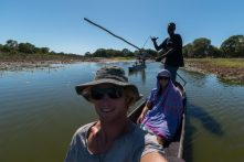 Selfie in the Mokoro, Dan in front Tegan behind with a sarong over her, Poler standing up with his pole doing a shaka hand
