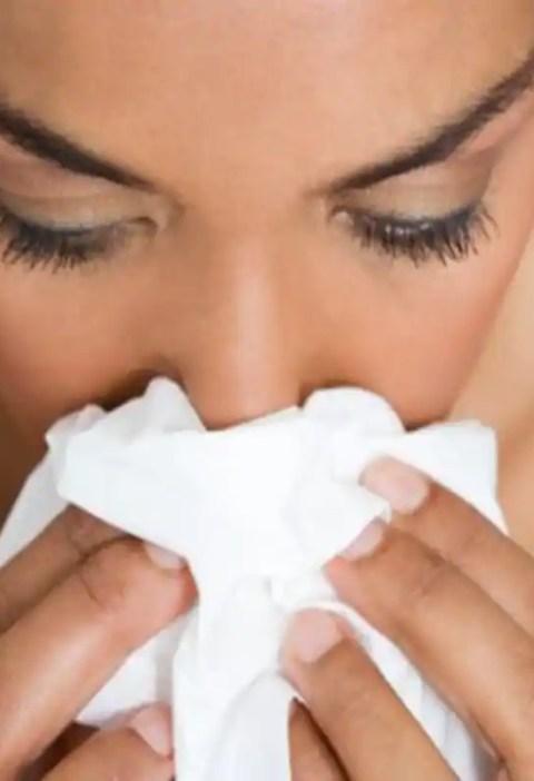 femeie care isi sufla nasul, rinita alergica, viroza, nas infundat