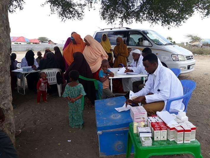 Lääkärin vastaanotto, kuvassa naisia lapsineen sekä lääkäri ja sairaanhoitovälineitä
