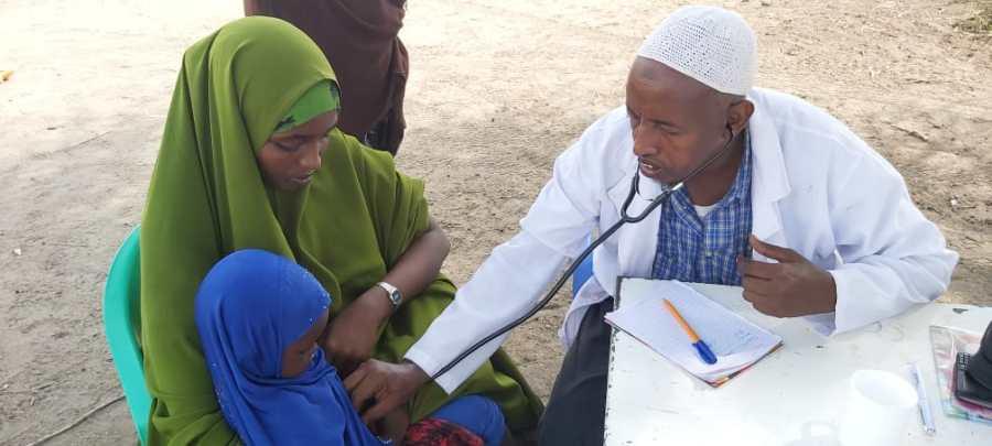 Mieslääkäri tutkii stetoskoopilla lapsipotilasta, joka istuu äidin sylissä.