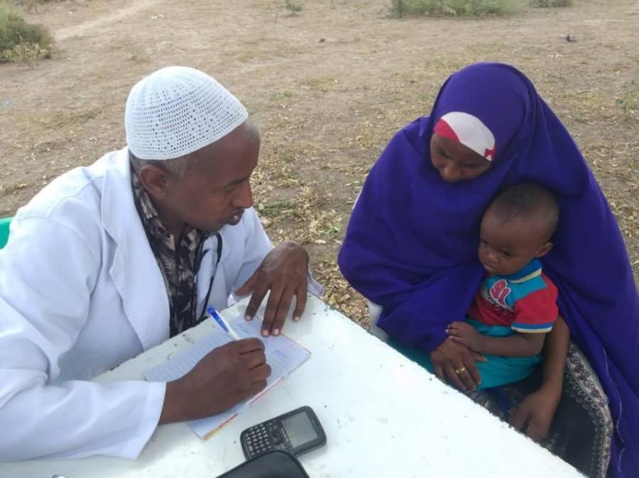 Miessairaanhoitaja neuvoo äitiä ja pientä lasta terveysasioissa.