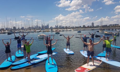 group of people standing up during their stand up paddle board lesson in Melbourne
