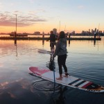 2 persons stand up paddle boarding at sunset after hiring a board in St kilda beach