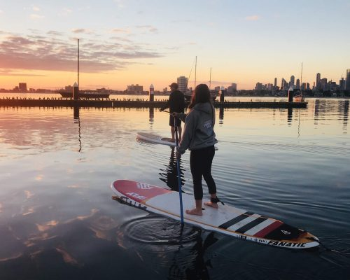 two paddler standing on a paddle board after hire board in St kilda