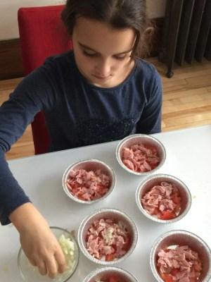 Louison remplit les petits moules des mini-quiches