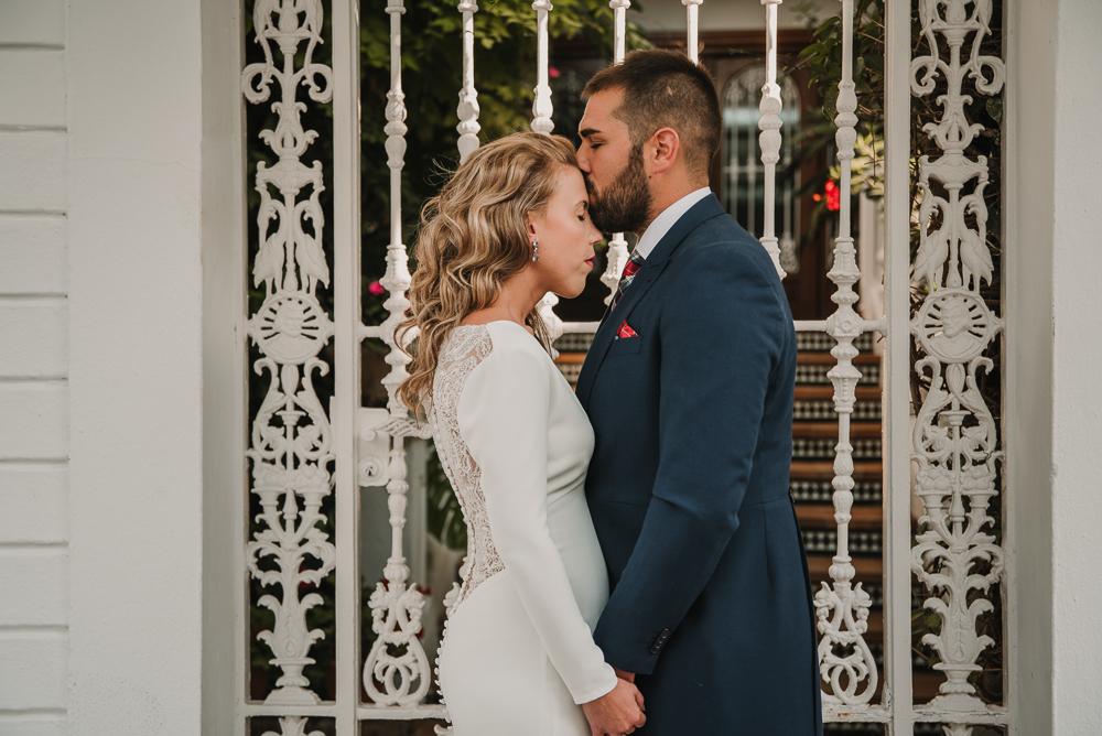 Novio besando en la frente a su pareja al lado de una reja blanca, fotografía de postboda en Nerja, Supercastizo