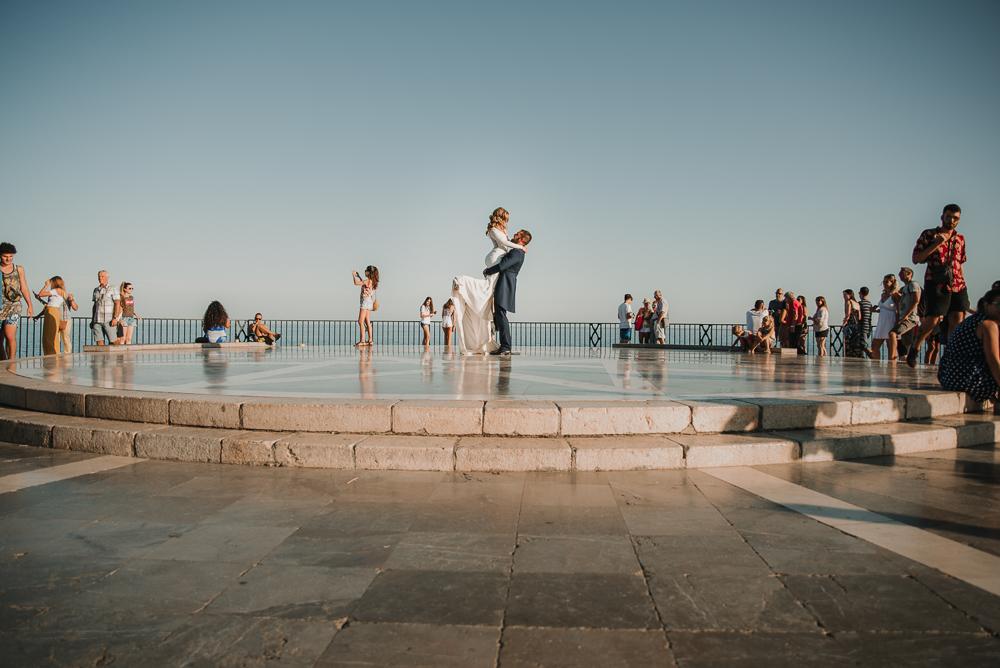 Novio cogiendo en brazos a su pareja en el balcón de España mientras la gente los mira, fotografía de postboda en Nerja , Supercastizo