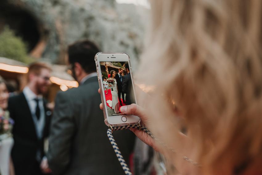 invitado fotografiando con movil a los novios