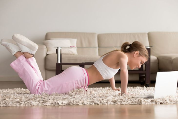 woman working out at home on her laptop