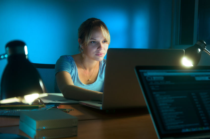 Photo of a woman at night, with a couple of different desk lights around her, as she works away on a laptop.