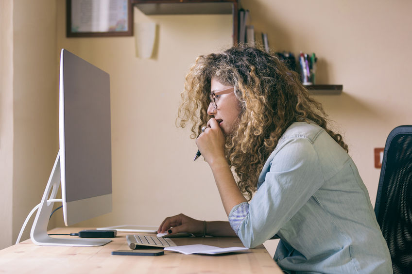 Photo of woman leaning over to look at a computer screen, with a pen in her mouth.