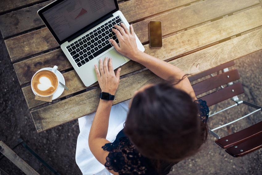Photo, shot overhead, of a young woman at a wooden table (looks like a picnic table) with a laptop computer; her smartphone is at the right of the laptop on the table, and at her left is a coffee drink in a cup that has some foam in the shape of a heart.