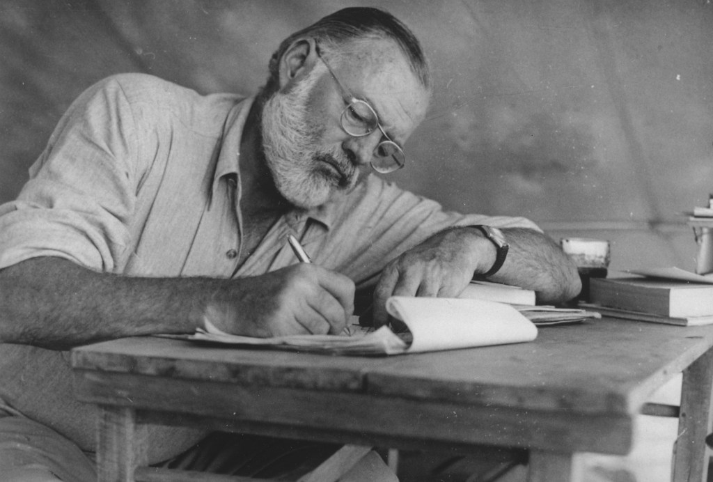 Black-and-white photo of Ernest Hemingway writing at a desk, 1953.