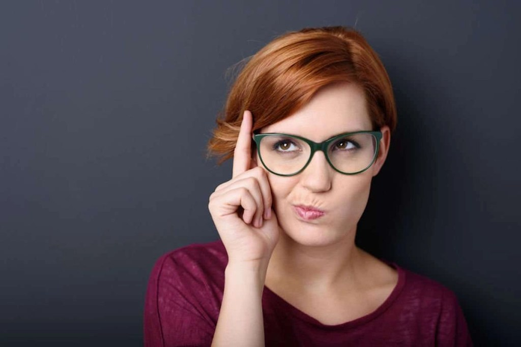 Photo of a woman with red hair wearing geeky glasses standing against a dark gray backdrop thinking with her finger raised, lips pursed, and a grimace of concentration in a humorous stereotypical depiction.