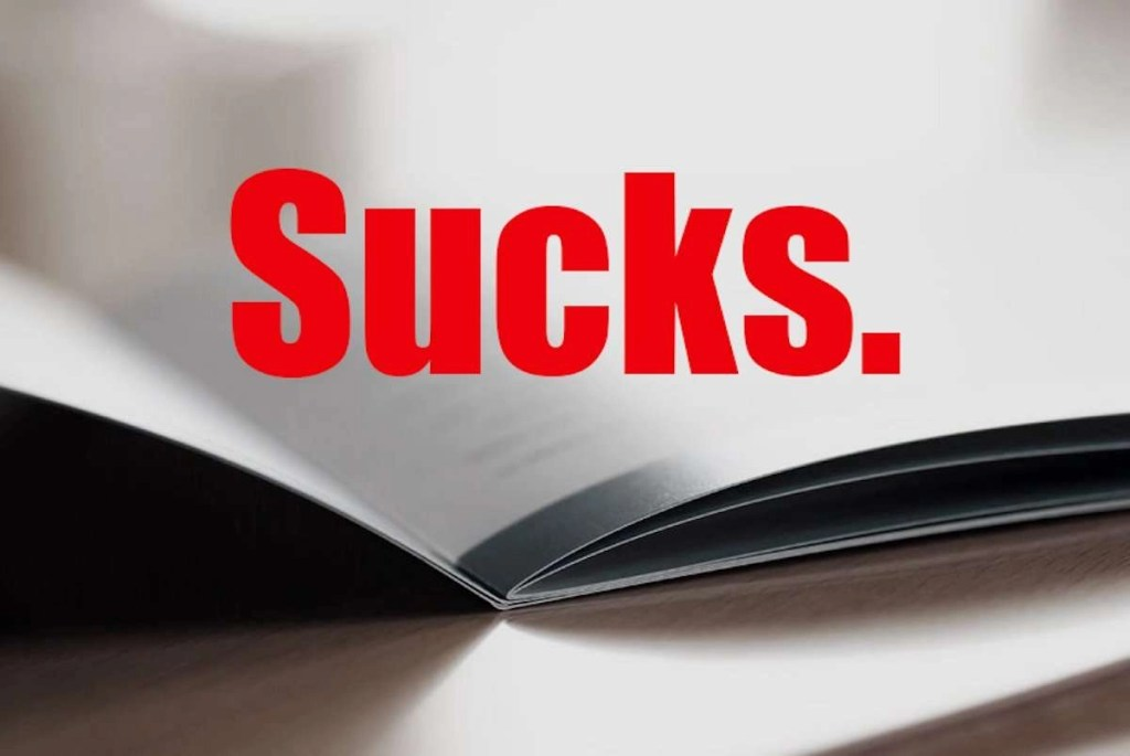 """Photo of an opened brochure closeup on a brown desk; the text is obscured and blurred. Overlaid over this photo is the word """"Sucks."""" in big bold red letters."""