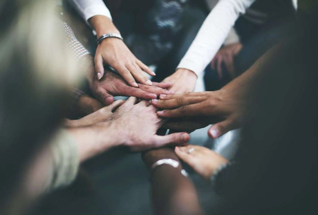 Photo of joined hands of a few different business workers in an office setting to illustrate the idea of teamwork.