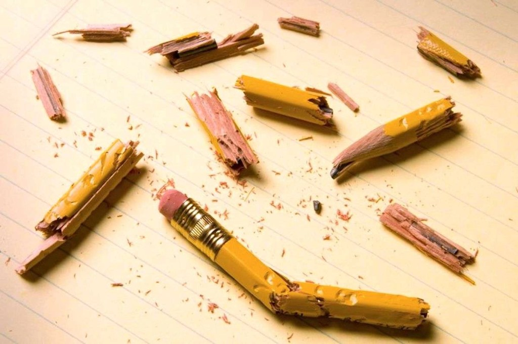 Photo of shattered pencil fragments on a yellow legal pad, perhaps symbolizing writer's block.