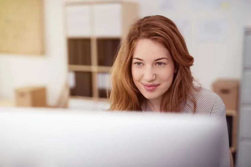 Photo of a young woman working on a desktop computer smiling as she leans forwards reading text on the screen.