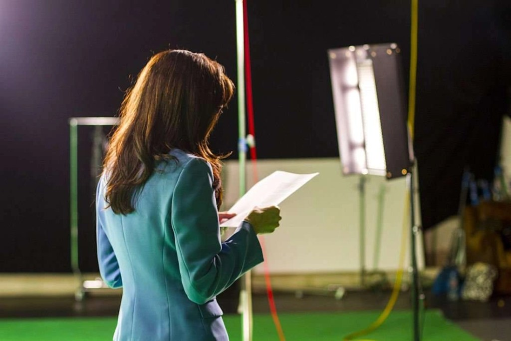 Photo of an actress holding a script, rehearsing on set with camera lights in the background.