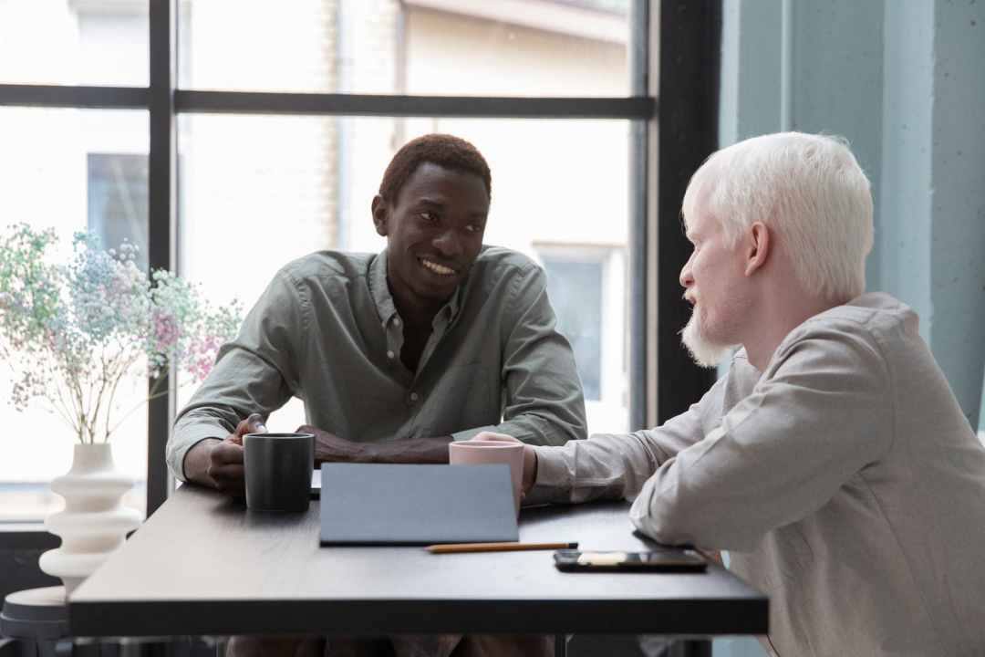 cheerful black man with colleague at table