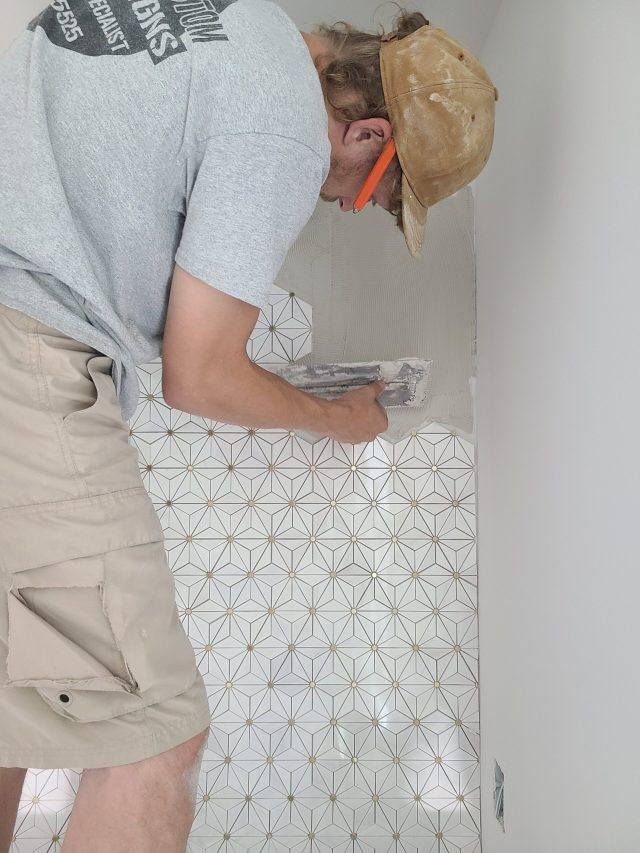 Co-Owner and Master Tile Setter lays intricate tile pattern