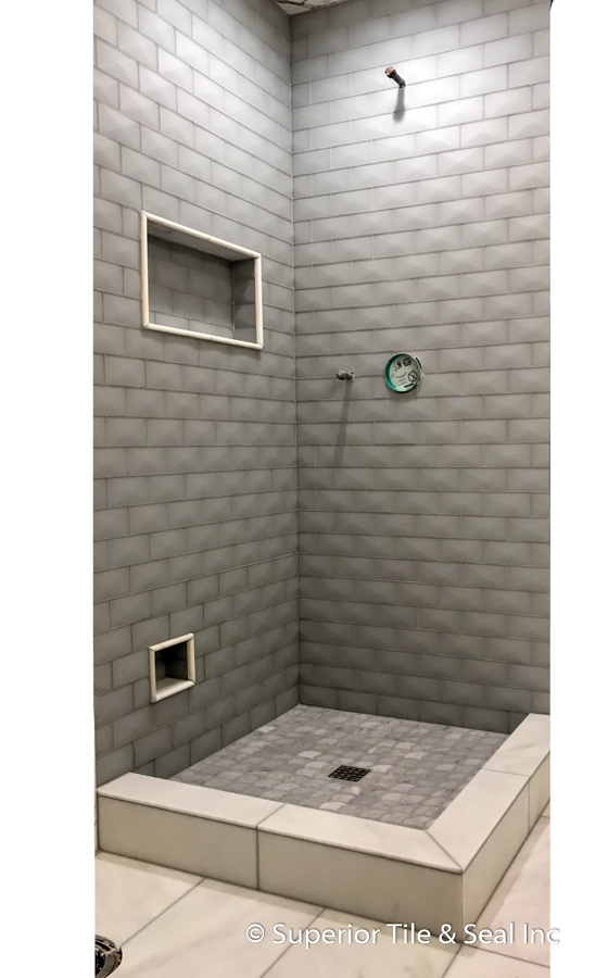 glass tile shower with carrara marble