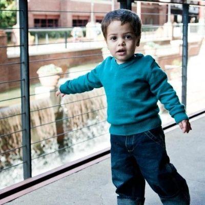 A toddler boy walks around on a patio exploring