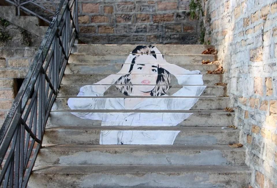 """L'œuvre """"Tribute to Gustave Courbet"""", créé en 2016 par Don Mateo. Se trouvant sur un escalier dans le quartier lyonnais de la croix-Rousse, il représente une jeune femme qui se touche les cheveux"""