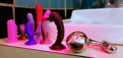[Image: njoy Pure Plug Large stainless steel butt plug on a bathroom sink next to silicone Funkit tiny dildos]