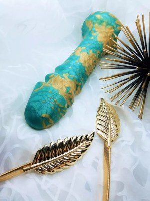 Image: a look at the Uberrime Aqua-King's silicone marbling of teal and gold. Because these dildos are handmade, no two have the exact same swirling patterns