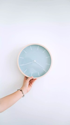 [Image: a hand holding a white clock]
