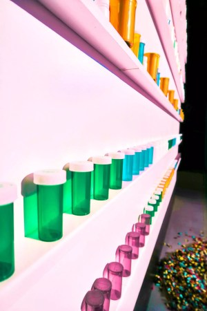 [Image: an assortment of pill bottles of different colors on shelves]