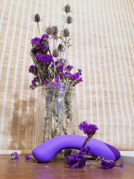 [Image: purple Blush Novelties Wellness G Ball G-spot vibrator in front of jar of dried purple flowers]