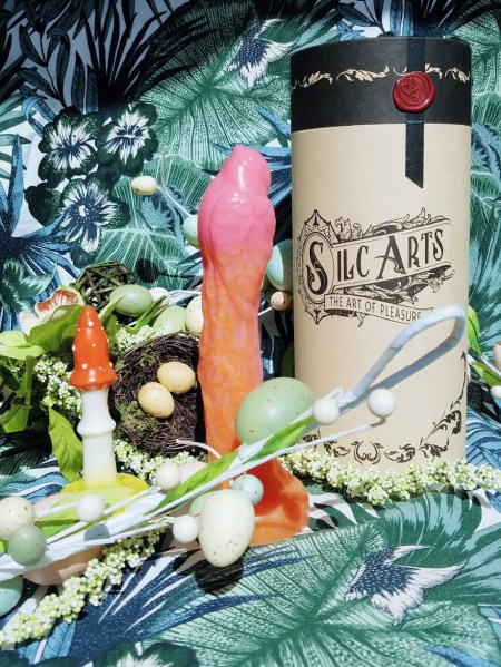 [Image: Self Delve Amanita Muscaria / Fly Agaric textured mushroom butt plug / dildo next to orange and pink Silc Arts Sparrow and Silc Arts cardboard canister packaging.]