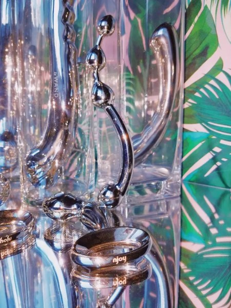 Stainless steel dildos and plugs on mirrors and in glass vases