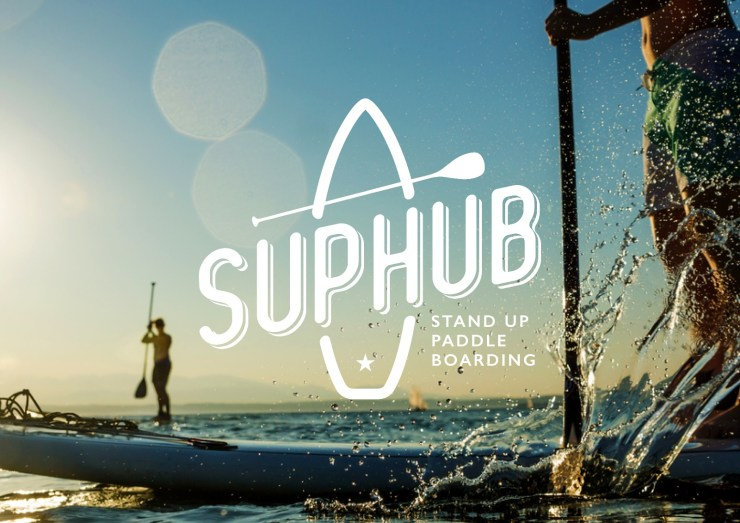 A couple stand up paddleboarding at sea with SUPHubNI logo