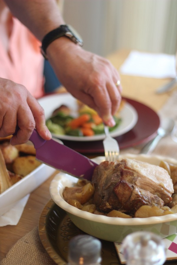 Carving the pork roast with apples and cider gravy