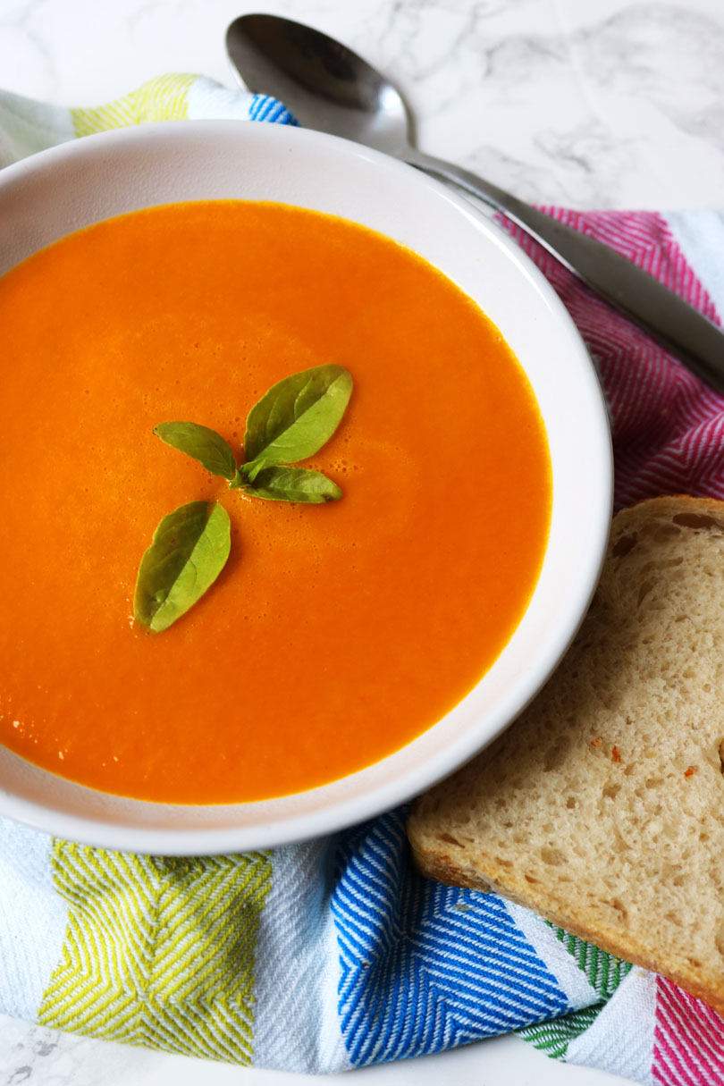 A hearty bowl of roasted tomato soup with a hunk of white bread and basil garnish from Supper in the Suburbs.