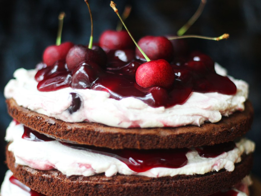 Close up of Black Forest Cake topped with fresh cherries and lashings of cream