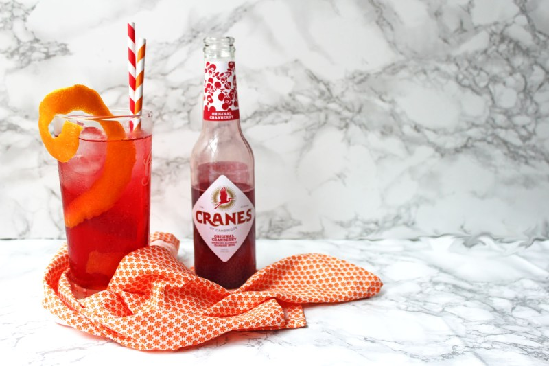 This summer try the hottest new lo alcohol trend, Cranes Cranberry Cider, as part of this Cranberry and Orange Cooler a long, low alcohol cocktail from Supper in the Suburbs. It's ideal for garden parties, BBQs and festivals!