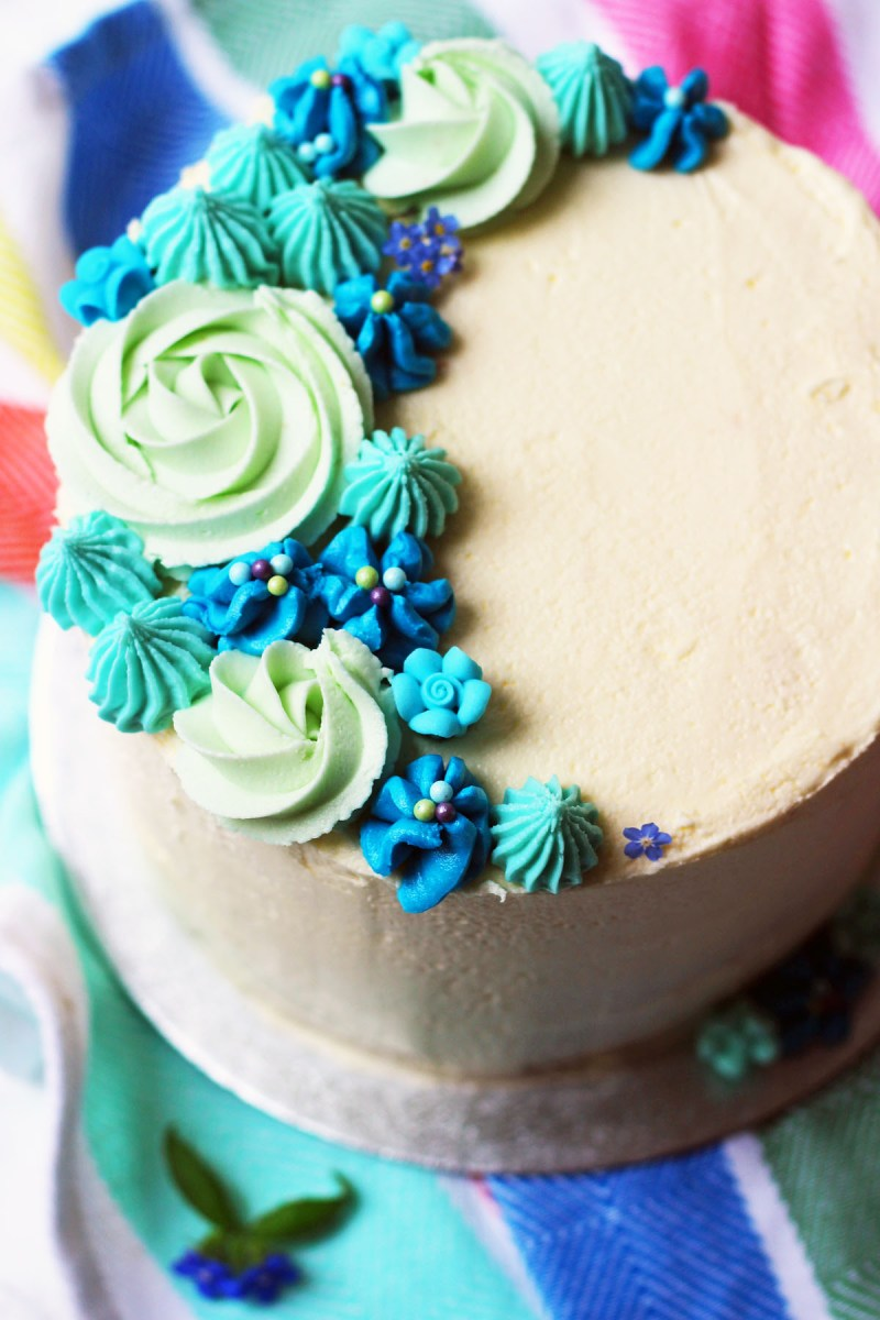 This stunning Lemon and Blueberry Layer Cake is the perfect spring celebration! Decorated with beautiful piped buttercream flowers and roses its a showstopping dessert. Get the recipe on Supper in the Suburbs!