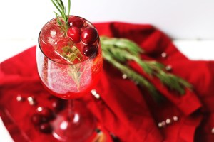 A single glass of Cranberry and Aperol Spritz, a Christmas Cocktail garnished with fresh cranberries and rosemary.