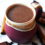 An earthenware mug of spiced hot chocolate spiked with cinnamon and amaretto.