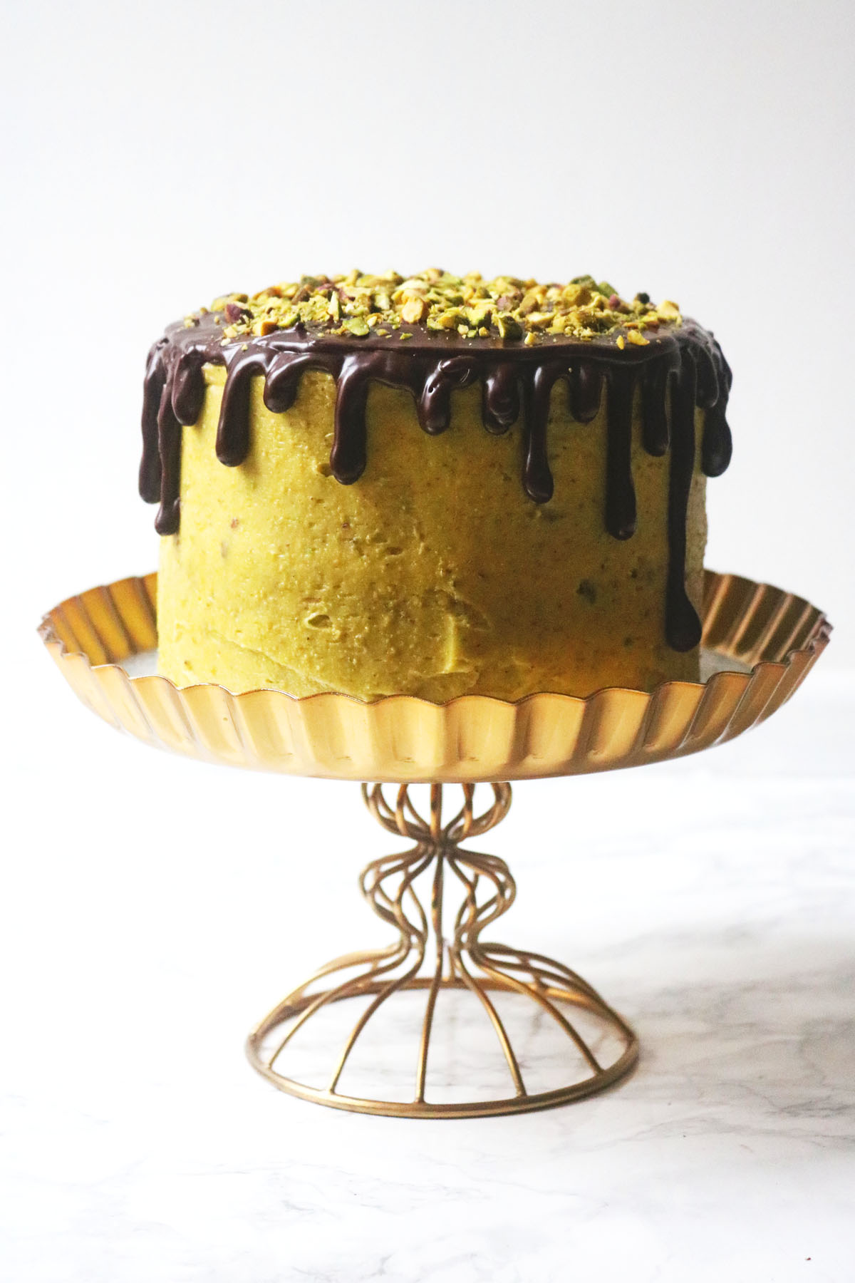 Chocolate and Pistachio Cake on a gold cake stand