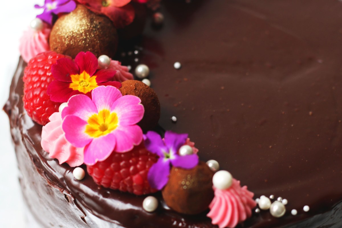 Close up of raspberries and edible flowers on top of a chocolate ganache covered cake