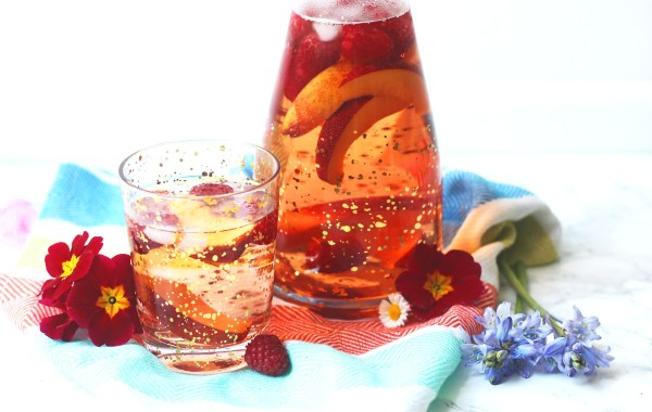 Glass of rose sangria, poured over raspberries and nectarine wedges
